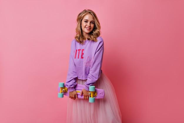 ロングボードでポーズをとる巻き毛の髪型を持つ興味のあるブロンドの女の子。ピンクの上に立っている紫色のシャツの洗練された白人女性。