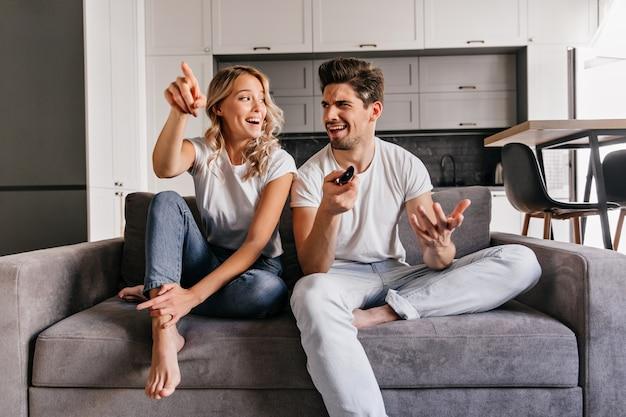 興味のある金髪の女性がテレビを見る。居心地の良いソファに座っている笑顔のカップルの屋内の肖像画。