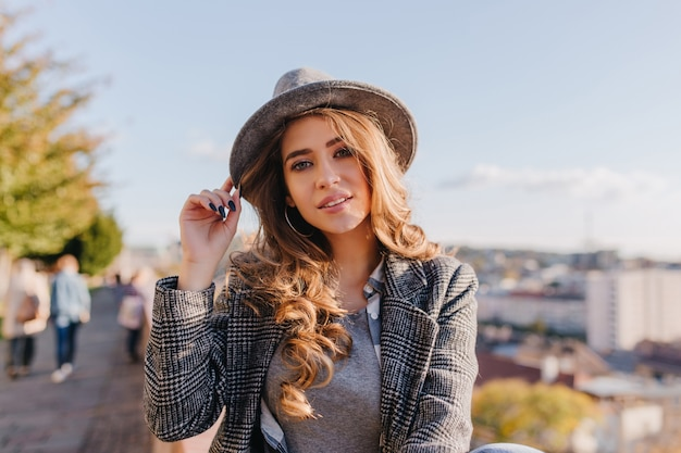 아침 산책 중에 포즈를 취하는 유행 모자에 관심있는 파란 눈의 여성