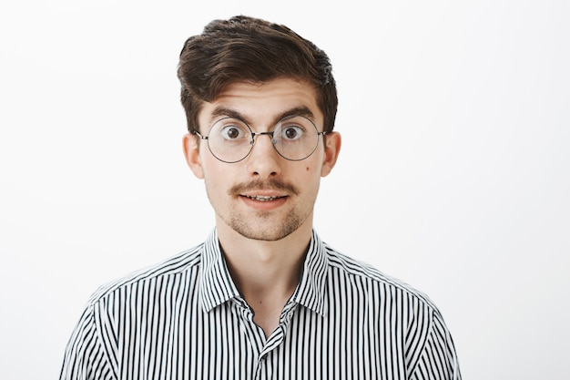 Interested bookworm wants buy new book in store. portrait of excited timid european male model with moustache and beard in glasses, lifting eyebrows from surprise, listening carefully over gray wall