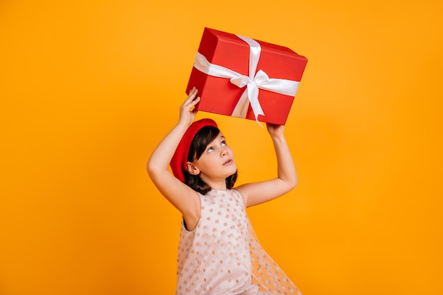 Interested brunette kid guessing what in present.  little girl in red hat holding gift on yellow wall.