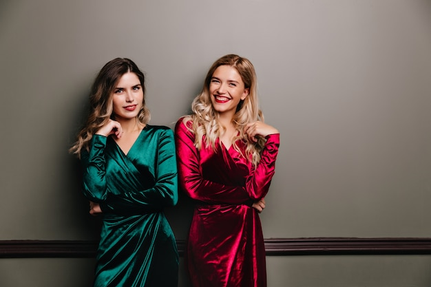 Interested brunette woman in green outfit standing on gray wall. indoor shot of lovely caucasian girls spending time at photoshoot.