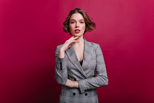 Interested businesswoman with trendy makeup posing on claret wall. indoor photo of serious young lady in tweed jacket standing in confident pose.