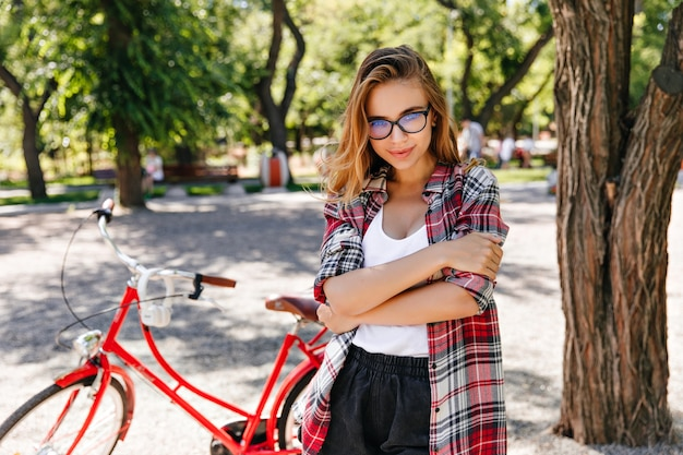 Interested caucasian girl in checkered shirt posing in park in summer day. good-humoured blonde woman chilling after bike ride.