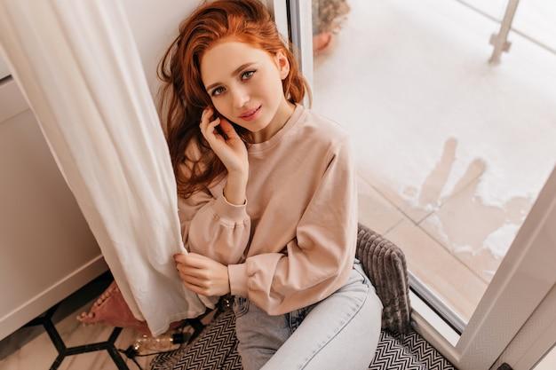 窓枠に座っている興味のある白人の女の子。家で身も凍るようなリラックスした生姜の女性。