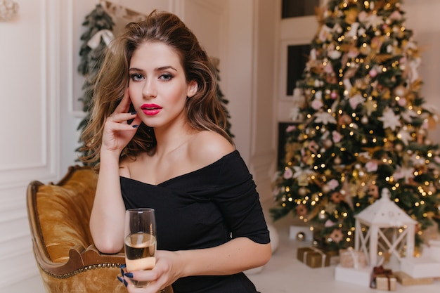 Interested caucasian girl with blue eyes posing on sofa in front of beautiful christmas tree. indoor portrait of good-looking brunette woman in black holding wineglass.