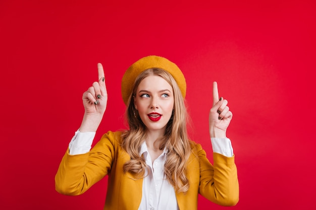 Signora caucasica interessata in berretto giallo rivolto verso l'alto con le dita. ragazza francese sveglia che gesturing sulla parete rossa.