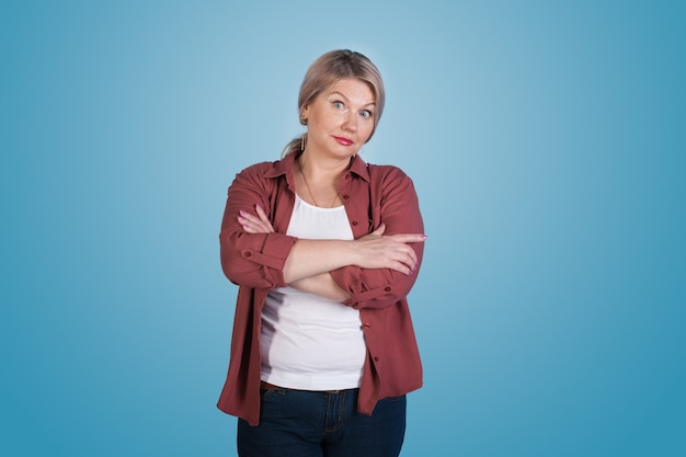 Interested caucasian senior woman with blonde hair posing with crossed hands on blue  wall