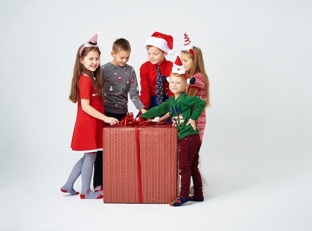 興味のある子供たちが巨大な贈り物を開く