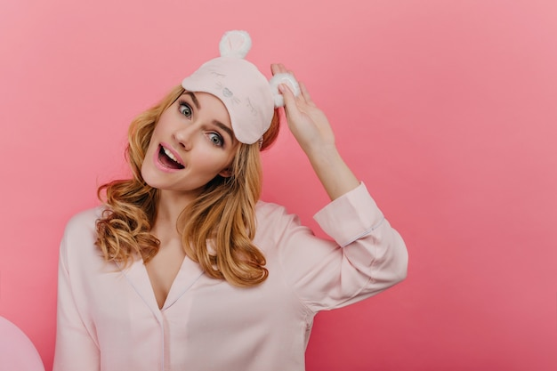 大きな目で笑っている興味のある巻き毛の女性。明るい壁に驚きの感情を表現するアイマスクの夢のような若い女性モデル。