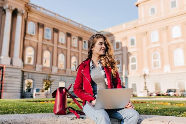 관심있는 검은 머리 소녀는 대학 근처 공원에서 차가워지고 노트북을 사용하는 캐주얼 복장을 착용합니다.