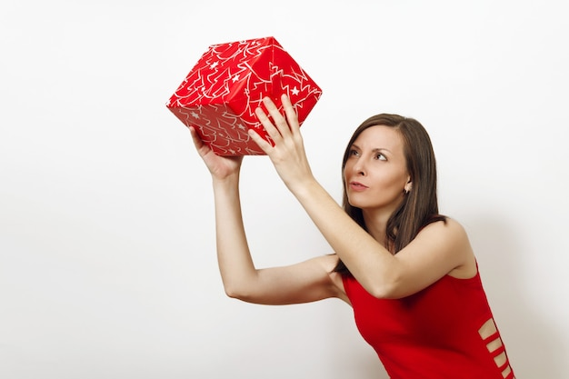 Interested and engaged young woman dressed in red dress and christmas hat holds gift box, thinks that she was given on white background. santa girl with present isolated. new year holiday 2018 concept