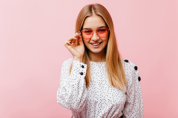 Interested european woman in sunglasses standing on pink. fascinating woman in white blouse having fun