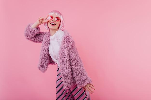 Ragazza divertente interessata in parrucchiere e occhiali da sole in posa con il segno di pace. tiro al coperto di beata donna caucasica indossa giacca soffice e peruke rosa