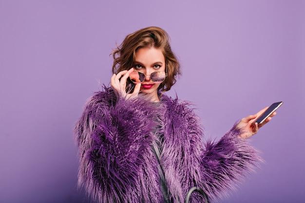 Заинтересованная девушка в стильной фиолетовой шубе смотрит в камеру с блестящими солнцезащитными очками