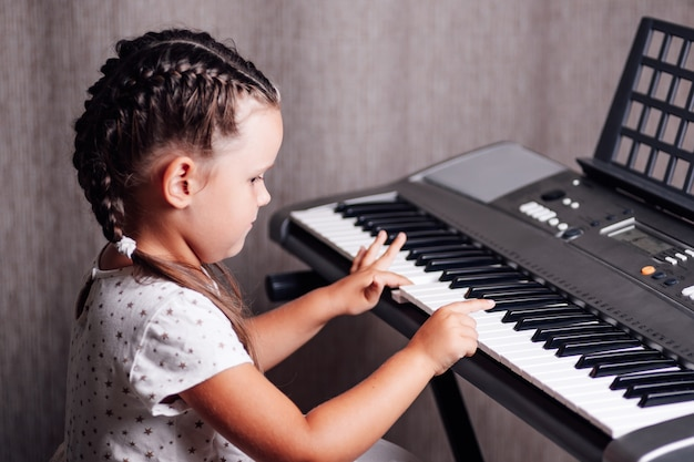 Interested girl learning to play an electronic synthesizer