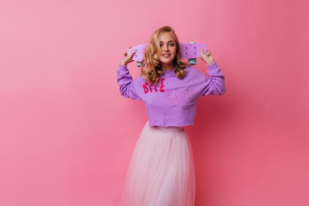 Ragazza interessata in gonna lunga e lussureggiante con un sorriso gentile. ritratto dell'interno di adorabile modello femminile con skateboard rosa.