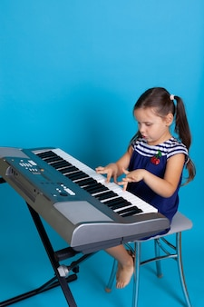 Interested girl playing a melody on the keys of an electronic synthesizer