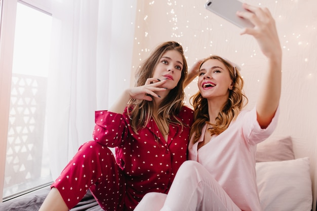 Interested girl in red night-suit looking to friend's phone while she taking picture of her. glad blonde woman in pink pajamas using smartphone for selfie.