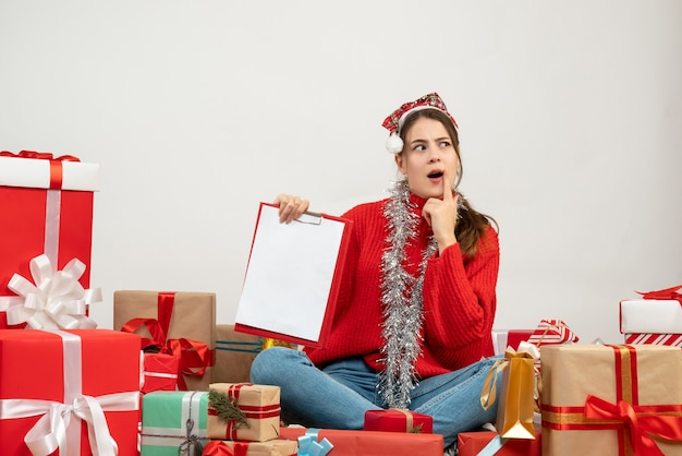 Interested girl with santa hat holding document sitting around presents on white