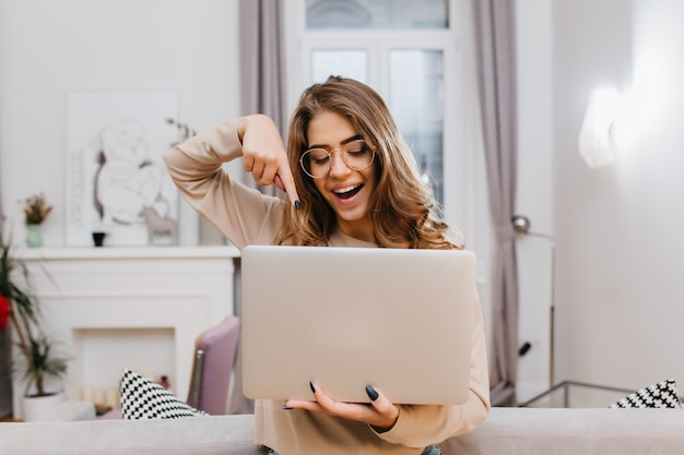 Interested girl with trendy manicure fooling around at home during photoshoot with laptop