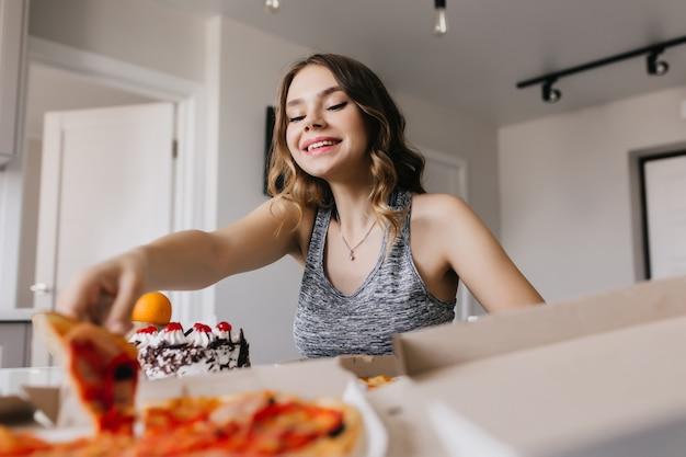 喜んでピザを食べるウェーブのかかった髪型の興味のある女の子。キッチンに座ってファーストフードを楽しむ華やかな女性モデル。