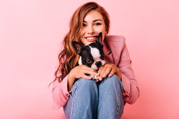 Заинтересованная девушка с волнистой прической проводит свободное время с собакой. портрет молодой женщины, позирующей с французским бульдогом.