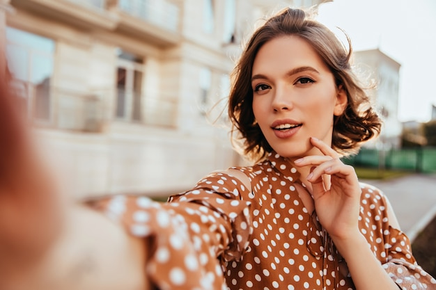 Donna affascinante interessata in abbigliamento marrone che fa selfie. magnifica ragazza bruna che si prende una foto mentre cammina per la città.