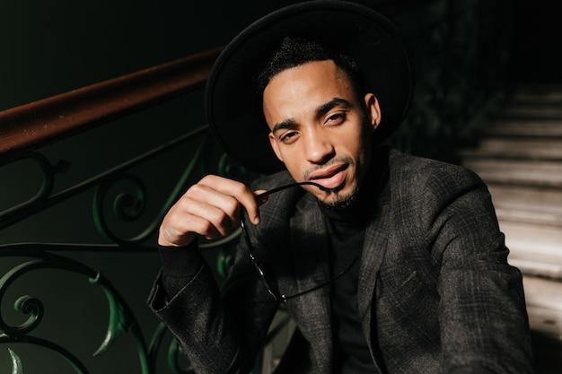 Заинтересованный красивый темнокожий мужчина ищет. восторженная молодая мужская модель в шляпе, сидя на лестнице.