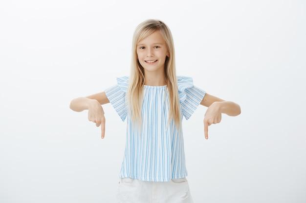 공정한 머리를 가진 관심있는 행복한 어린 소녀, 집게 손가락으로 아래를 가리키고 넓게 웃고, 회색 벽 위에 자신감 있고 편안합니다.
