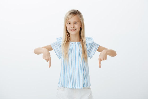 Interested happy young girl with fair hair, pointing down with index fingers and smiling broadly, being self-assured and relaxed over gray wall