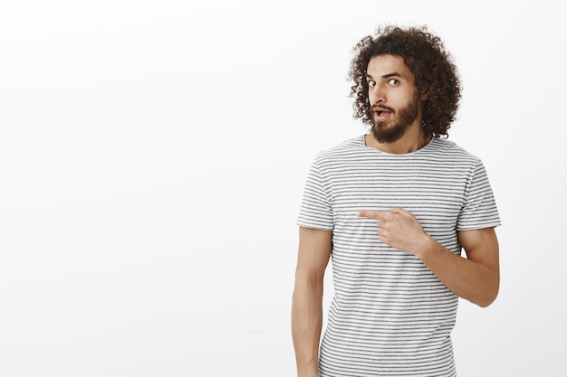 Interested hot hispanic guy with beard and afro hairstyle, pointing right while saying wow or asking question, being curious and questioned about person