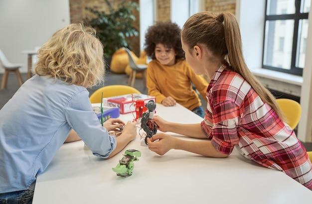 Заинтересованные в технологиях счастливые дети изучают, глядя на технические игрушки на столе, полном