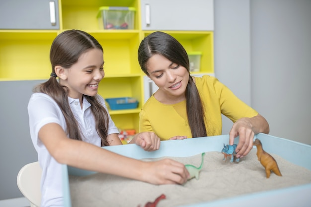 Interested joyful school-age girl and young woman playing with small animal figurines in sand tray