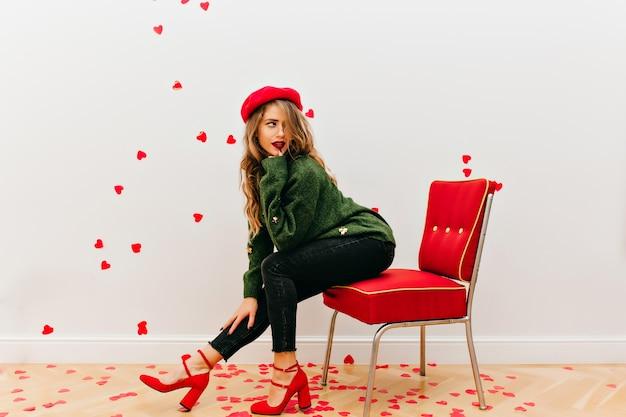 ハートで飾られたスタジオでポーズをとる緑のセーターに興味のある格好の良い女性
