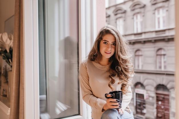 Заинтересованная застенчивая женщина с длинными волосами позирует с чашкой чая на подоконнике