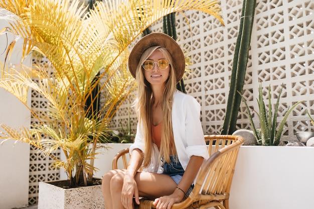 リゾートカフェに座っている長い髪型の興味のあるスリムな女性。晴れた日に屋外レストランでリラックスした黄色のサングラスの愛らしい女性モデル。