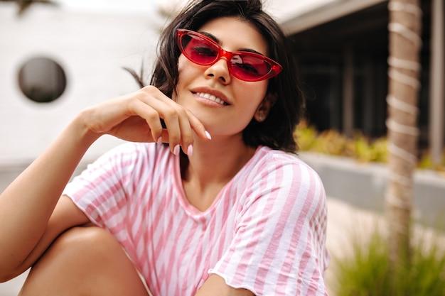 카메라를보고 스트라이프 티셔츠에 관심이 웃는 여자. 거리 배경에 선글라스에 평온한 무두 질된 아가씨의 야외 촬영.