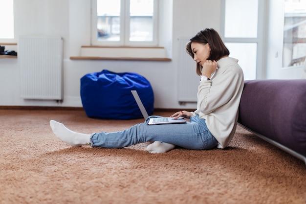 興味のある学生の女性は、カジュアルな服装で昼間の家の床に座っているラップトップコンピューターで動作します