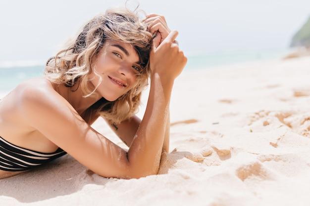 해변에서 즐기는 관심이 무두 질된 여자. debonair 젊은 여자는 리조트에서 시간을 보내고.