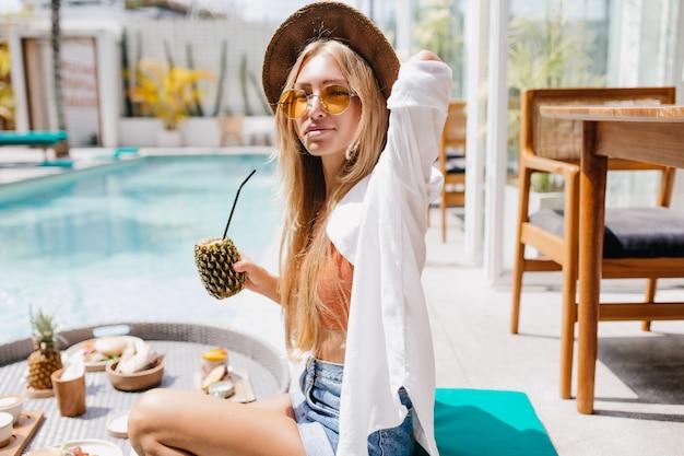 여름 아침에 수영장 근처 칵테일을 마시는 흰 셔츠에 관심이 무두 질된 여자. 사랑스러운 금발의 여자는 리조트에서 주말에 과일을 먹는 모자를 착용합니다.