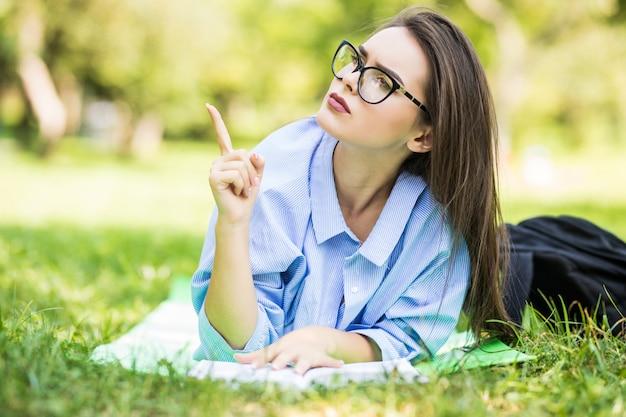 Заинтересованная девочка-подросток, лежа на траве в парке с ручкой и блокнотом