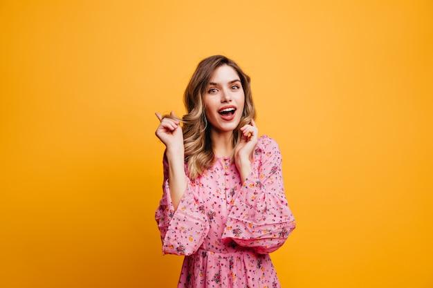Interessato ragazza bianca con acconciatura ondulata che esprime interesse. foto dell'interno della magnifica donna romantica in abito rosa.