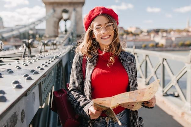 赤いセーターとベレー帽に興味のある白人女性が屋外で時間を過ごし、地図で街を探索