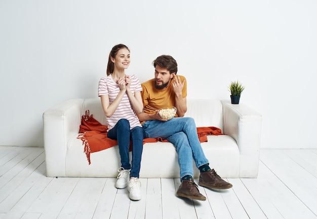 Заинтересованная женщина и бородатый мужчина сидят на диване, попкорн в тарелке и цветок в горшке.