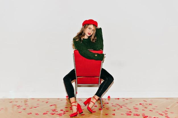 Заинтересованная женщина со светло-каштановыми длинными волосами позирует на красном стуле