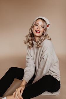 笑顔で正面を向いている光沢のあるカールを持つ興味のある女性