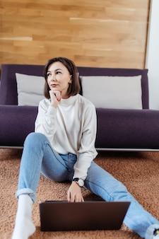Заинтересованная женщина работает на ноутбуке, сидя на полу дома в дневное время одет
