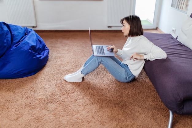 Заинтересованная женщина работает на ноутбуке, сидя на полу возле черного дивана