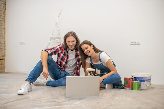 興味がある。床に座って、ラップトップで何かを見ている若いカップル